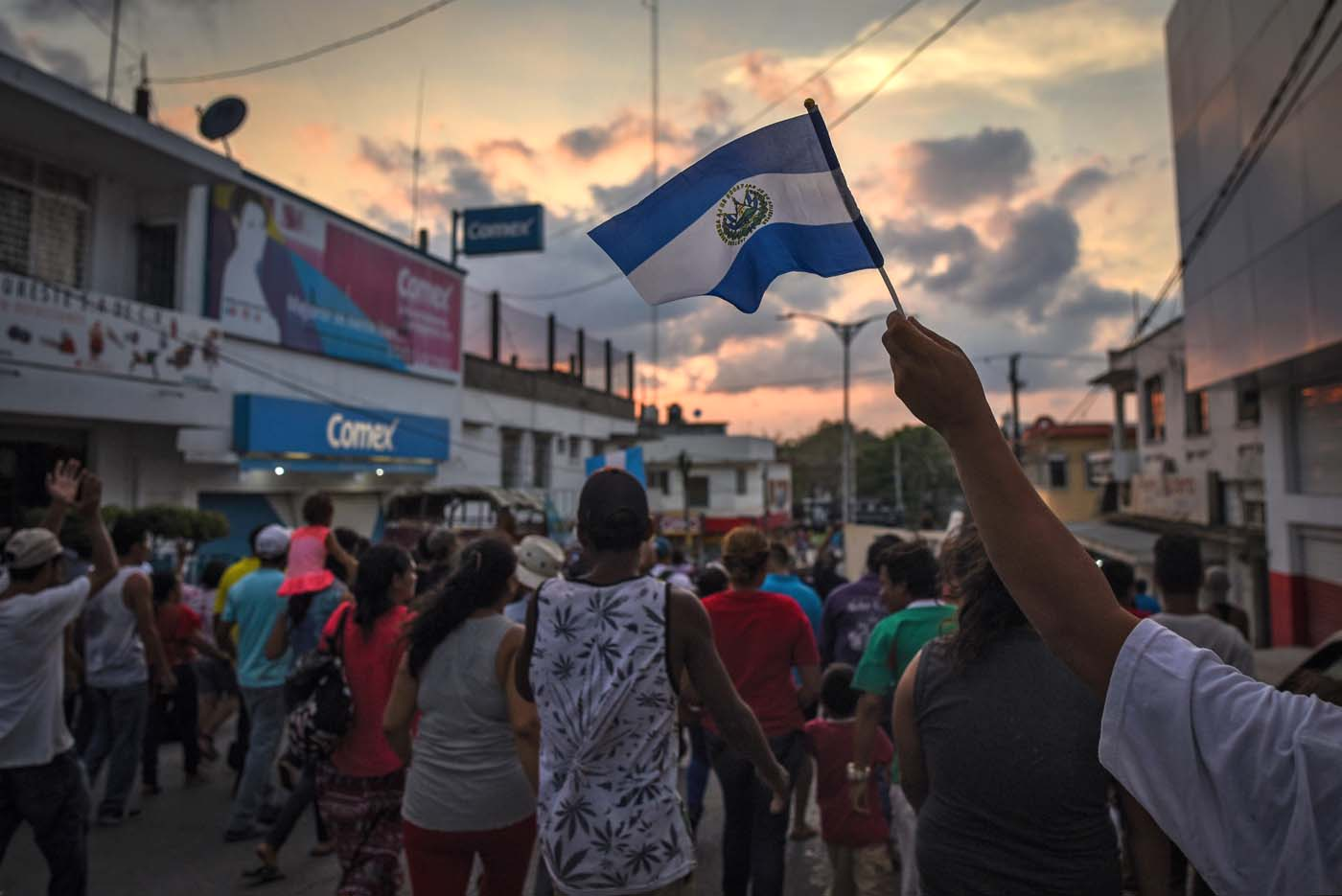 """A migrant -alongside other Central Americans taking part in a caravan called """"Migrant Viacrucis"""" towards the United States- flutters a Guatemalan national flag during a march to protest against US President Donald Trump's policies in Matias Romero, Oaxaca State, Mexico, on April 3, 2018. The hundreds of Central Americans in the """"Way of the Cross"""" migrant caravan have infuriated Trump, but they are not moving very fast -- if at all -- and remain far from the US border. As Trump vowed Tuesday to send troops to secure the southern US border, the caravan was camped out for the third straight day in the town of Matias Romero, in southern Mexico, more than 3,000 kilometers (1,800 miles) from the United States. / AFP PHOTO / VICTORIA RAZO"""