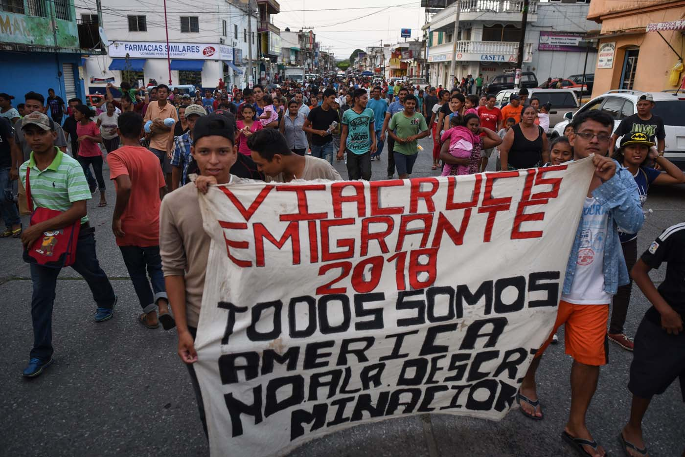 """Central American migrants taking part in a caravan called """"Migrant Viacrucis"""" towards the United States hold a banner reading """"Emigrant Viacrucis 2018. We are all America. No to discrimination"""" as they march to protest against US President Donald Trump's policies in Matias Romero, Oaxaca State, Mexico, on April 3, 2018. The hundreds of Central Americans in the """"Way of the Cross"""" migrant caravan have infuriated Trump, but they are not moving very fast -- if at all -- and remain far from the US border. As Trump vowed Tuesday to send troops to secure the southern US border, the caravan was camped out for the third straight day in the town of Matias Romero, in southern Mexico, more than 3,000 kilometers (1,800 miles) from the United States. / AFP PHOTO / VICTORIA RAZO"""