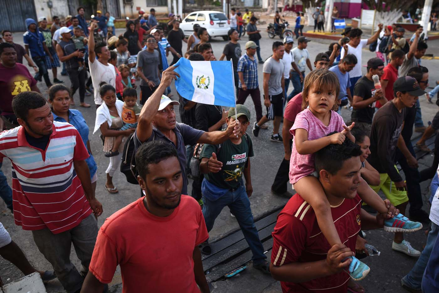 """A migrant -alongside other Central Americans taking part in a caravan called """"Migrant Viacrucis"""" towards the United States- holds a Guatemalan national flag during a march to protest against US President Donald Trump's policies in Matias Romero, Oaxaca State, Mexico, on April 3, 2018. The hundreds of Central Americans in the """"Way of the Cross"""" migrant caravan have infuriated Trump, but they are not moving very fast -- if at all -- and remain far from the US border. As Trump vowed Tuesday to send troops to secure the southern US border, the caravan was camped out for the third straight day in the town of Matias Romero, in southern Mexico, more than 3,000 kilometers (1,800 miles) from the United States. / AFP PHOTO / VICTORIA RAZO"""
