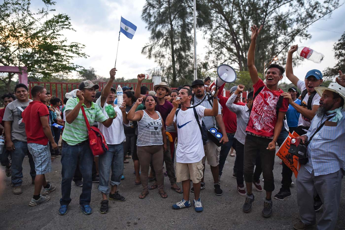 """A migrant with a loudspeaker -alongside other Central Americans taking part in a caravan called """"Migrant Viacrucis"""" towards the United States- takes part in a march to protest against US President Donald Trump's policies in Matias Romero, Oaxaca State, Mexico, on April 3, 2018. The hundreds of Central Americans in the """"Way of the Cross"""" migrant caravan have infuriated Trump, but they are not moving very fast -- if at all -- and remain far from the US border. As Trump vowed Tuesday to send troops to secure the southern US border, the caravan was camped out for the third straight day in the town of Matias Romero, in southern Mexico, more than 3,000 kilometers (1,800 miles) from the United States. / AFP PHOTO / VICTORIA RAZO"""