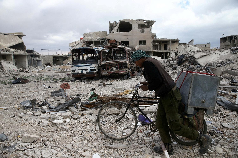 Un hombre camina junto a su bicicleta en un sitio dañado en la sitiada ciudad de Douma, en Guta oriental, en Damasco, Siria, el 30 de marzo de 2018. REUTERS/Bassam Khabieh TPX IMAGES OF THE DAY - RC1D8D2702B0