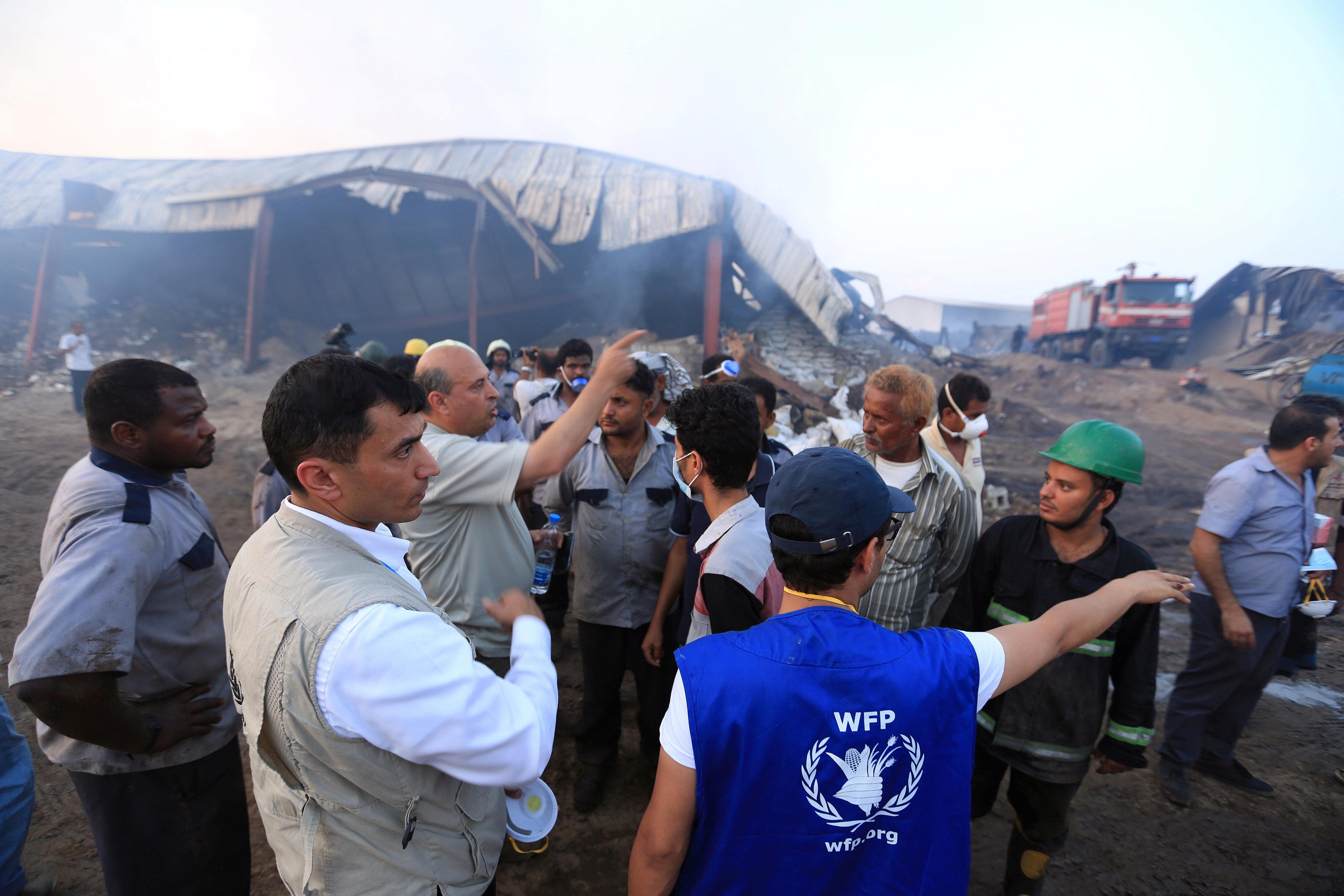 Los trabajadores humanitarios inspeccionan un almacén del Programa Mundial de Alimentos un día después de que el fuego lo envolvió en la ciudad portuaria de Hodeida, Yemen, el 1 de abril de 2018. REUTERS / Abduljabbar Zeyad