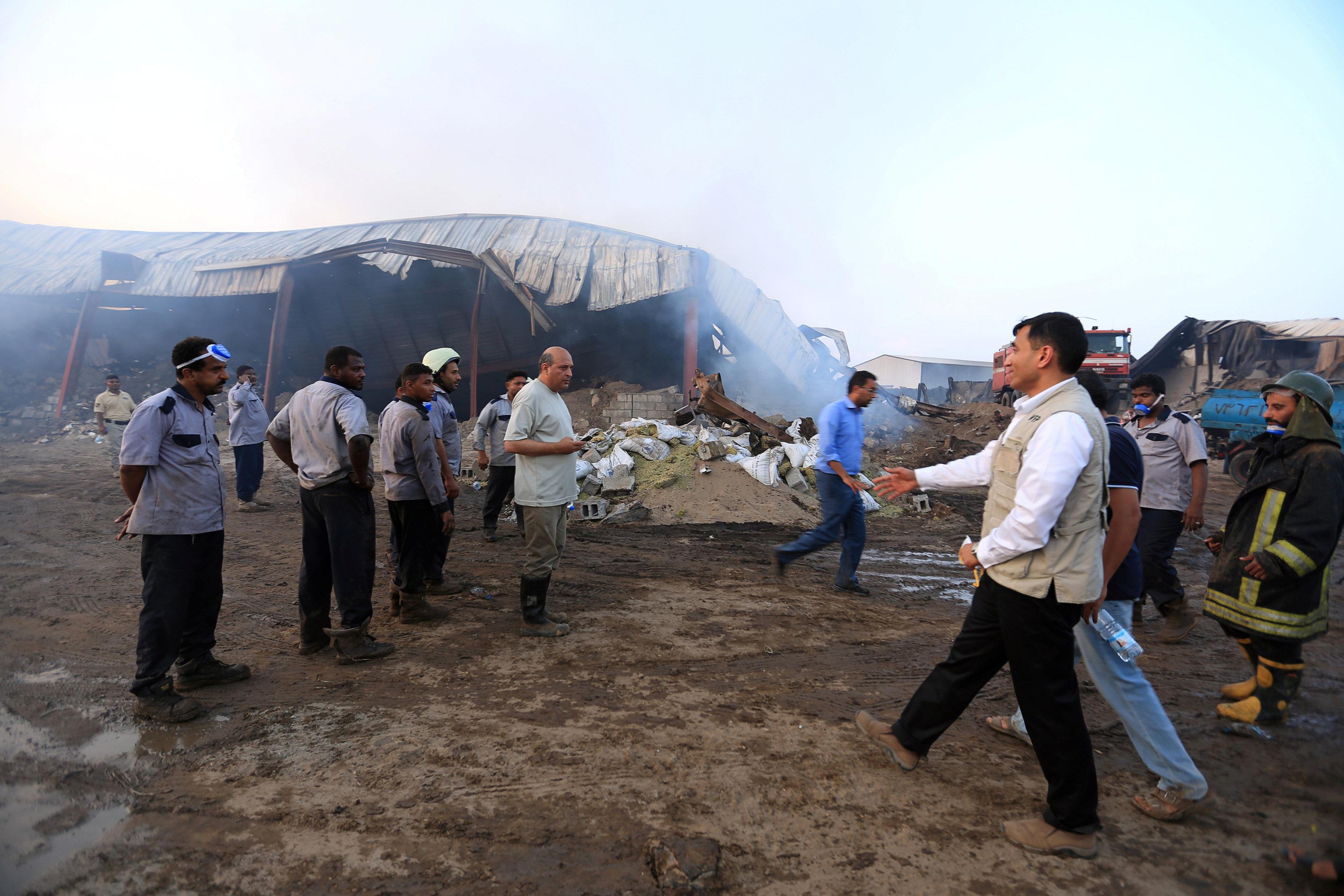 Los trabajadores humanitarios inspeccionan los almacenes del Programa Mundial de Alimentos un día después de que el fuego los envolviera en la ciudad portuaria de Hodeida, Yemen, el 1 de abril de 2018. REUTERS / Abduljabbar Zeyad