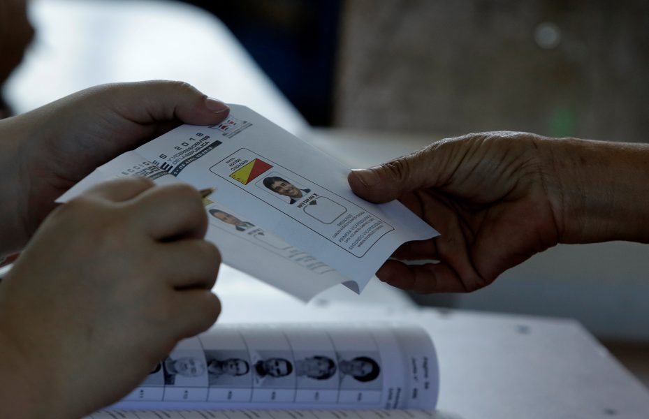 A voter gets a ballot during the presidential election at a polling station in San Jose, Costa Rica, April 1, 2018. REUTERS/Juan Carlos Ulate