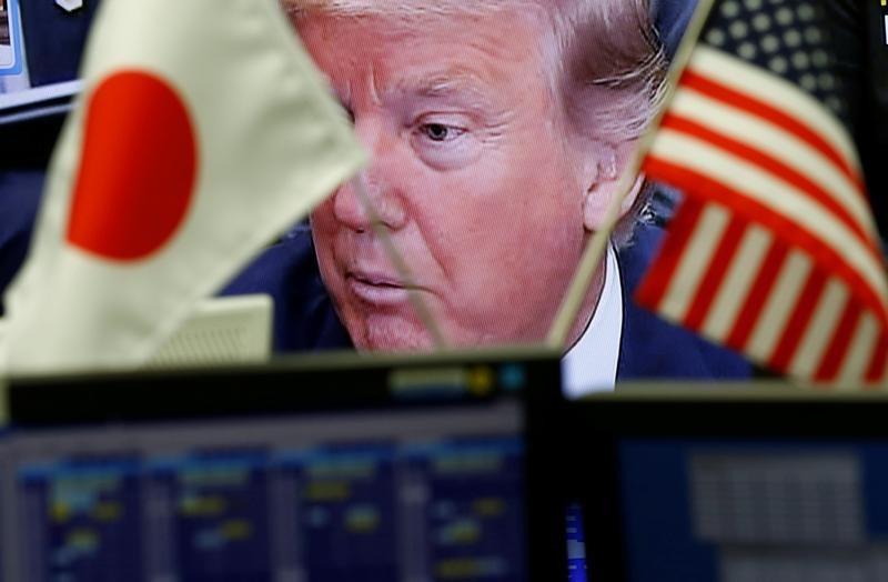 En la imagern de archivo un monitor de televisión muestra al presidente estadounidense Donald Trump detrás de las banderas nacionales de EE. UU. Y Japón en una empresa comercializadora de divisas en Tokio, Japón, el 1 de febrero de 2017. REUTERS / Kim Kyung-Hoon