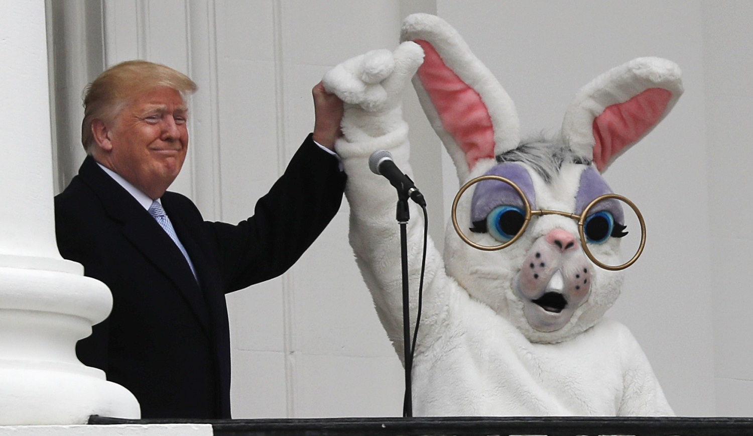 U.S. President Donald Trump raises the arm of the Easter Bunny as they appear together on the South Portico of the White House during the annual White House Easter Egg Roll on the South Lawn of the White House in Washington, U.S., April 2, 2018. REUTERS/Carlos Barria