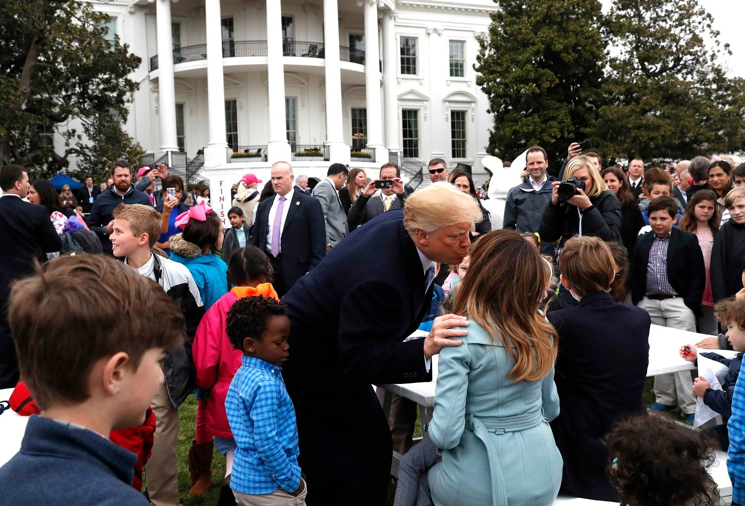 U.S. President Donald Trump kisses first lady Melania Trump among children gathered for the annual White House Easter Egg Roll on the South Lawn of the White House in Washington, U.S., April 2, 2018. REUTERS/Leah Millis