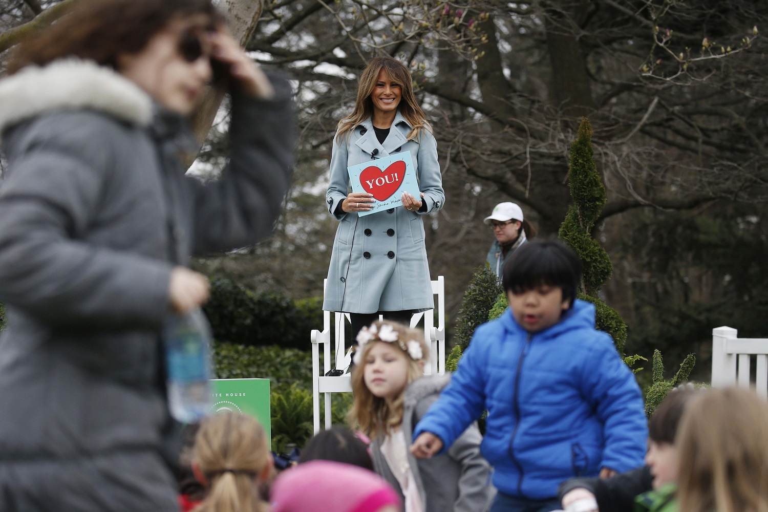 """Children and U.S. first lady Melania Trump stand up after she read Sandra Boynton's book """"You!"""" to children gathered for the annual White House Easter Egg Roll on the South Lawn of the White House in Washington, U.S., April 2, 2018. REUTERS/Leah Millis"""