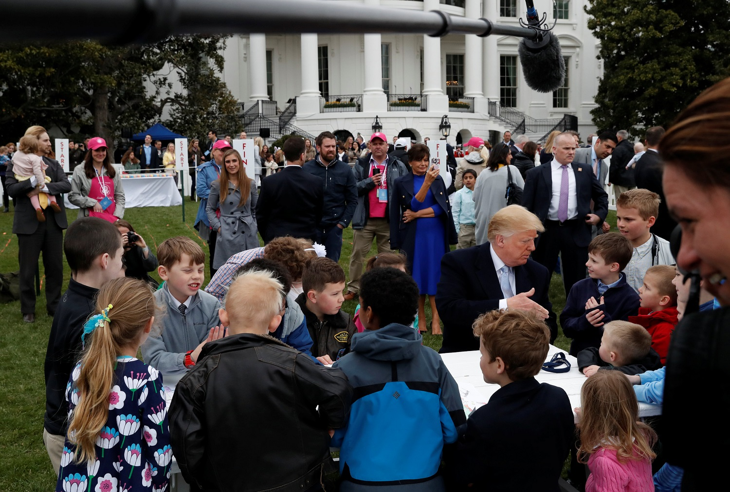 U.S. President Donald Trump greets children after they made drawings for U.S. military members during the annual White House Easter Egg Roll on the South Lawn of the White House in Washington, April 2, 2018. REUTERS/Leah Millis