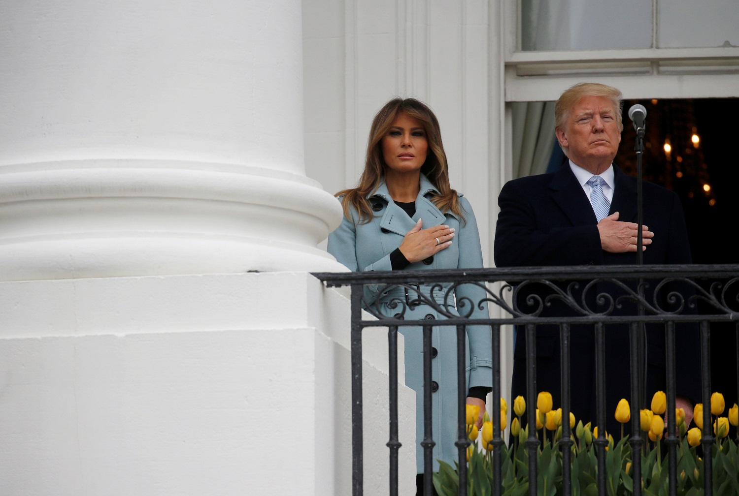 U.S. President Donald Trump and first lady Melania Trump listen to the national anthem during the annual White House Easter Egg Roll on the South Lawn of the White House in Washington, April 2, 2018. REUTERS/Leah Millis