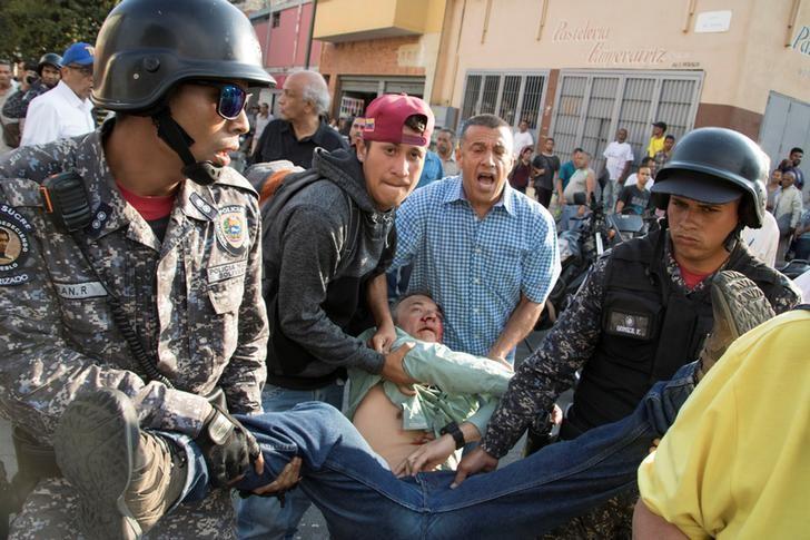 Teodoro Campos, legislador opositor y jefe de seguridad del candidato presidencial venezolano Henri Falcón, recibe ayuda luego de sufrir una lesión durante un mitin de Falcón en Caracas, Venezuela, 2 de abril del 2018. REUTERS/Rayner Peña