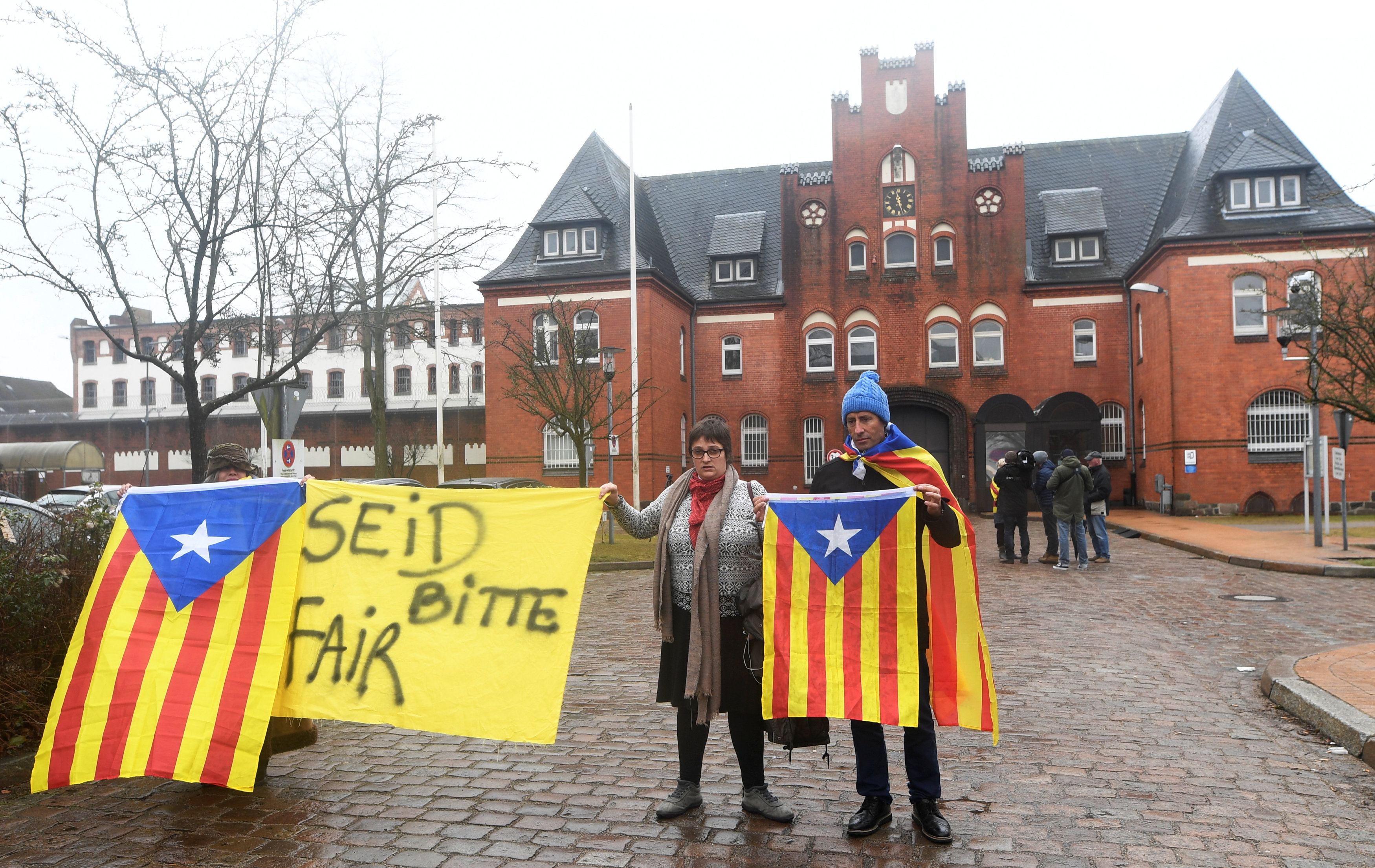 """People hold a poster and Estelada (Catalan separatist flag) in protest to support the release of former Catalan regional president Carles Puigdemont in front of the prison in Neumuenster, Germany, April 3, 2018.  The poster reads """"Be fair please""""    REUTERS/Fabian Bimmer"""