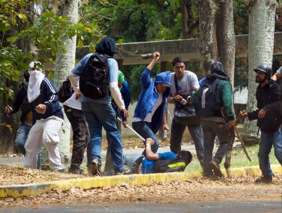 Un estudiante opositor, tendido en el suelo, es atacado por un grupo pro gubernamental dentro de la Universidad de Venezuela, durante una manifestación contra el gobierno el jueves 3 de abril de 2014 en Caracas, Venezuela. (Foto AP/Fernando Llano)