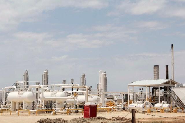 Una planta de procesamiento de petróleo y gas alimentado por pozos de esquisto locales se representa a lo largo de una carretera en las afueras de Carrizo Springs, cerca de 30 millas (48 km) de la frontera con México (David Alire / Reuters)