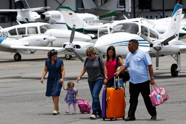 Passengers walk at the airstrip as they arrive at Charallave airport outside Caracas