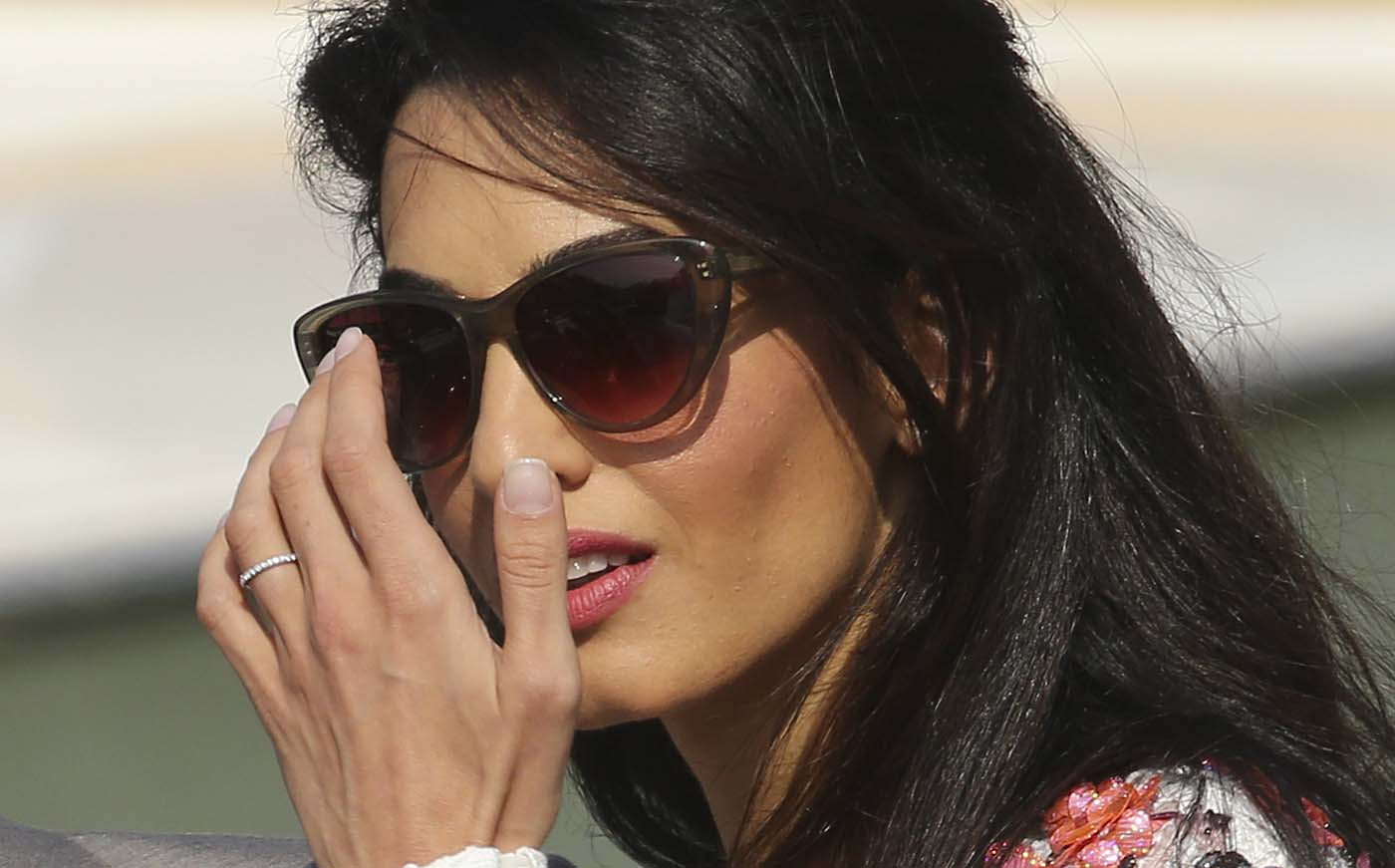 A wedding ring is seen on the hand of Alamuddin as she