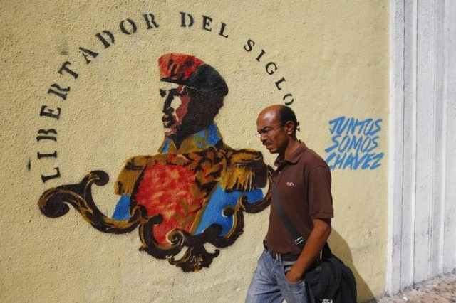 Imagen de archivo de un hombre pasando junto a un grafiti alusivo a la figura del ex presidente venezolano Hugo Chávez en el aniversario de su muerte en Caracas