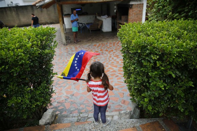 Matilda Medina waves the Venezuelan flag during a visit to bid goodbye in her grandparents' house, before her move to the U.S., in Valencia