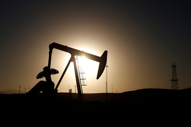 An oil derrick is seen at sunrise near Bakersfield