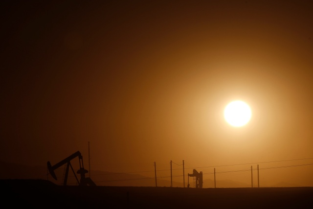 Oil derricks are seen at sunrise near Bakersfield