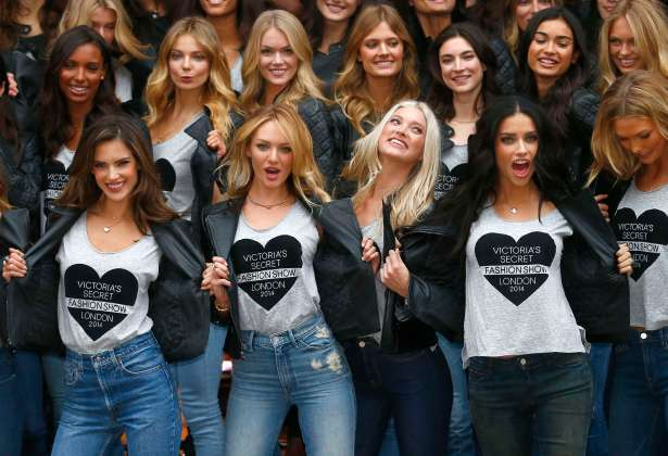 Models pose for a group photograph outside the Victoria's Secret shop on New Bond Street in central London