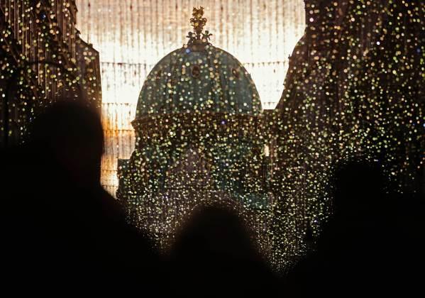 Visitors walk past Christmas lights towards Hofburg Palace's Michaeler Cupola in Vienna
