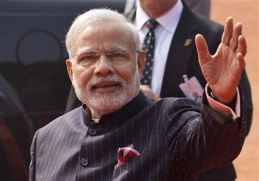 El primer ministro indio Narendra Modi viste un traje oscuro a rayas durante la visita que el presidente estadounidense Barack Obama hizo a la India en enero de 2015. Este mismo traje fue subastado por casi 700.000 dólares, se informó el viernes 20 de febrero de 2015. (Foto AP/Saurabh Das)