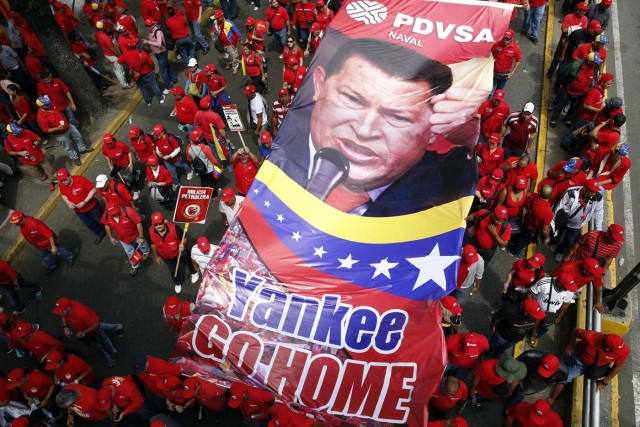 Workers of state-run oil company PDVSA hold a giant picture of Venezuela's late president Hugo Chavez during a rally against imperialism in Caracas