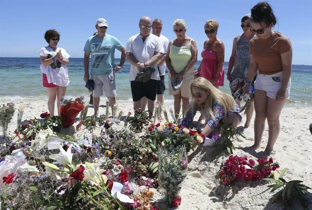 Varios turistas depositan flores en memoria de las víctimas en la playa situada frente al hotel Imperial Marhaba de Susa (Túnez) hoy, martes 30 de junio de 2015. El número de ciudadanos británicos muertos en el atentado del viernes en Túnez asciende a 21, pero se estima que hay otros nueve, informó hoy Downing Street, residencia oficial del primer ministro, David Cameron. EFE/Mohamed Messara