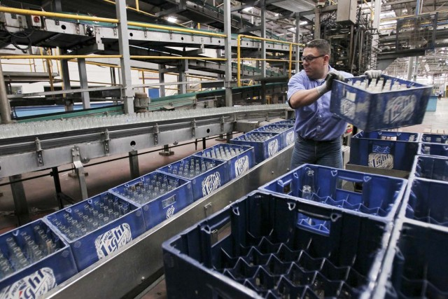 An employee carries beer boxes at a production line in a Polar brewery in Maracaibo, Venezuela July 13, 2015. Venezuela's Labor Ministry has ordered workers to lift a strike at beer maker Polar that had halted two of its breweries and restricted supplies of beer in the South American nation. Polar, the country's largest privately owned company, produces as much as 80 percent of the beer consumed in the country, which has historically been among the world's top per capita consumers of beer. Picture taken on July 13, 2015. REUTERS/Isaac Urrutia