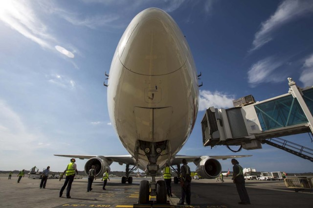 Workers stand next to an aircraft at a runway on the Simon Bolivar airport in Caracas July 17, 2015. Venezuelan airline Avior is purchasing 12 used planes to offer new international routes from the South American nation, where foreign carriers have slashed flights due to currency controls. Avior President Jorge Anez said in an interview on Thursday that the company was purchasing six planes from Europe's Airbus Group and six from Chicago-based Boeing CO for a total of about $150 million. REUTERS/Marco Bello