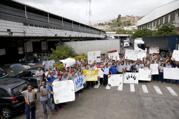 Empresas Polar workers hold placards and shout in a facility used by the company as a distribution center, during the occupation of its installations by government representatives in Caracas July 30, 2015. REUTERS/Carlos Garcia Rawlins