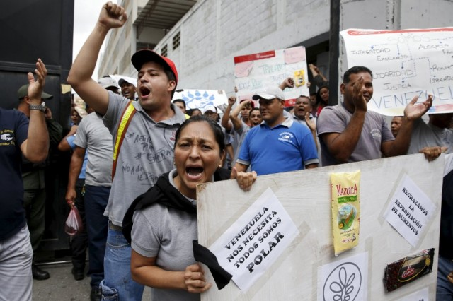 "Empresas Polar workers hold placards and shout at the gate of a facility used by the company as a distribution center, during the occupation of its installations by government representatives in Caracas July 30, 2015. The placard reads: ""Venezuela needs us, we are all Polar"". REUTERS/Carlos Garcia Rawlins"