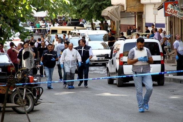 Police forensic experts examine the street following an attack on police officers in Diyarbakir, Turkey, July 23, 2015.  A Turkish police officer was shot and killed and a second wounded on Thursday in the mainly Kurdish city of Diyarbakir in the latest in a series of attacks that began with a suicide bombing blamed on Islamic State, security sources said. The shooting, which occurred in the centre of Diyarbakir, comes one day after two police officers were killed in an attack in Ceylanpinar on the Syrian border for which militants from the Kurdistan Workers Party (PKK) claimed responsibility. REUTERS/Sertac Kayar