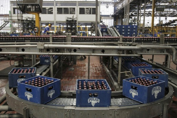 Beer boxes are seen at a production line at a Polar brewery in Maracaibo, Venezuela July 13, 2015. Venezuela's Labor Ministry has ordered workers to lift a strike at beer maker Polar that had halted two of its breweries and restricted supplies of beer in the South American nation. Polar, the country's largest privately owned company, produces as much as 80 percent of the beer consumed in the country, which has historically been among the world's top per capita consumers of beer. Picture taken on July 13, 2015. REUTERS/Isaac Urrutia