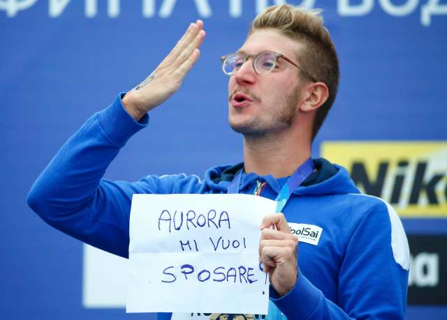 "Italian gold medalist Simone Ruffini blows a kiss into the crowd as he holds up a self-made paper reading ""Aurora do you want to marry me"" at the medal ceremony for the men's 25km open water race at the Aquatics World Championships in Kazan, Russia August 1, 2015.          REUTERS/Hannibal Hanschke"