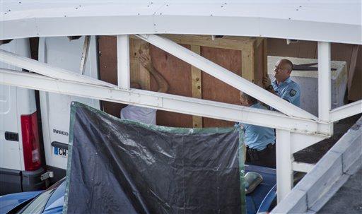 Miembros de la gendarmería francesa cargan una caja de madera que contiene parte del ala de un avión que apareció en las costas de la isla de Reunión, antes de ser trasladada a Francia, en el aeropuerto Roland Garros de Sainte-Marie, al norte de la isla, el 31 de julio de 2015. (Foto AP/Ben Curtis)