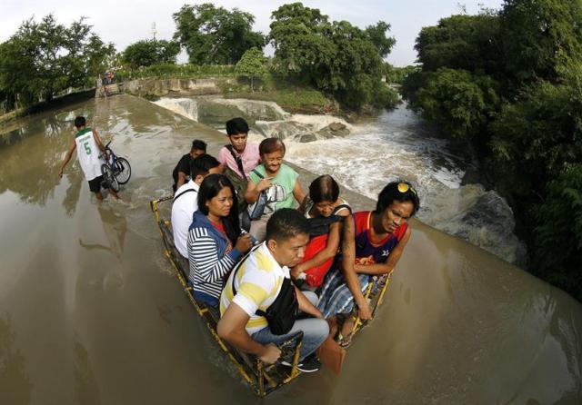 Varias personas cruzan un río desbordado en Las Pinas a las afueras de Manila (Filipinas) hoy 6 de agosto de 2015. Al menos siete personas han muerto y otras tres permanecen desaparecidas en las inundaciones. Además, el tifón Soudelor, el más intenso de 2015, se acerca a las islas de Batanes, en el extremo norte de Filipinas, por lo que las autoridades han activado la alerta meteorológica en la zona, informaron hoy fuentes gubernamentales. Aunque no se espera que el tifón llegue a las costas filipinas, PAGASA activó en Batanes el nivel de alerta 1, de un máximo de 4, lo que indica la posibilidad de vientos desde 30 a 60 kilómetros por hora y precipitaciones moderadas en los próximos días, que podrían causar inundaciones. Los expertos predicen que el tifón, bautizado con el nombre de Hanna por las autoridades locales, estará a 355 kilómetros de Itbayat, Batanes, el próximo sábado, y habrá salido de aguas filipinas el domingo en dirección hacia Taiwán y China. EFE/Francis R. Malasig
