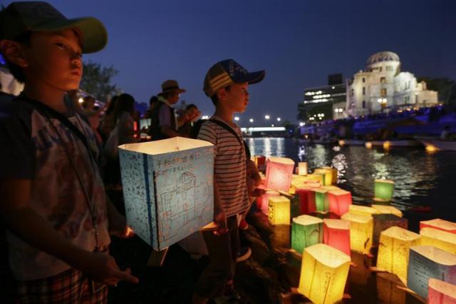 Un niño ilumina una linterna junto al río Motoyasu en memoria de las víctimas de la bomba atómica en el Parque de la Paz de Hiroshima (Japón) hoy 6 de agosto de 2015. La bomba lanzada por un avión estadounidense sobre la ciudad nipona acabó de forma inmediata con la vida de unas 80.000 personas, aunque este número aumentaría hacia finales de 1945, cuando el balance de muertos se elevaba a unos 140.000, y en los años posteriores las víctimas por la radiación sumaron muchas más. EFE/Kimimasa Mayama
