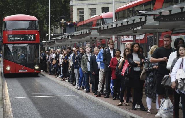 Una multitud de peatones esperan su autobús en Londres (Reino Unido) hoy 06 de agosto de 2015. Trabajadores de metro han convocado una huelga para hoy lo que ha ocasionado que millones de personas hayan tenido que buscar un transporte alternativo. EFE/Andy Rain