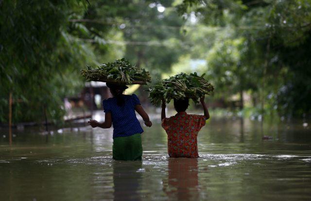 BIR02 DAR KA (BIRMANIA) 12/08/2015.- Dos mujeres caminan por las calles inundadas de Dar Ka (Birmania) hoy 12 de agosto de 2015. Casi un millón de personas se han visto damnificadas por las inundaciones que afectan gran parte de Birmania (Myanmar), provocadas por las intensas lluvias monzónicas que caen desde el mes pasado. El ministerio de Bienestar Social también indicó que el balance de víctimas ya superó el centenar, la mayoría de ellas en el estado Rakhine, en el oeste del país, según el diario Global New Light of Myanmar. EFE/Lynn Bo Bo
