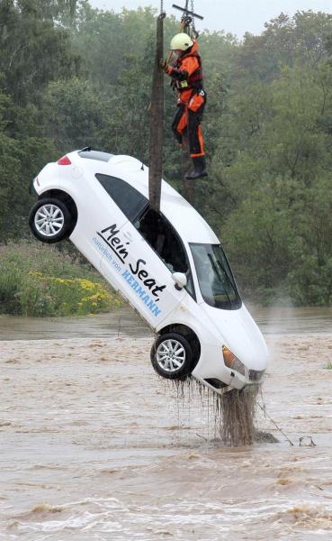 Un bombero saca del agua un coche en una zona inundada en Göttingen (Alemania) hoy, 17 de agosto de 2015. Los bomberos han trabajado toda la noche por las inundaciones causadas por las fuertes tormentas caídas en el sur del estado alemán de Baja Sajonia. EFE/Stefan Rampfel