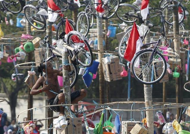 Un indonesio participa en un concurso de escalada de un poste para alcanzar los regalos dejados en lo alto durante las celebraciones por el 70º aniversario de la Independencia en el Palacio Presidencial Merkeda en Yakarta (Indonesia) hoy, 17 de agosto de 2015. EFE/Adi Weda