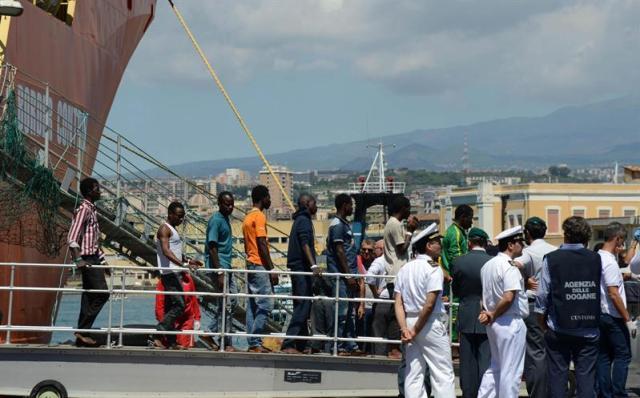 Los inmigrantes desembarcan del buque noruego Siem Pilot llega al puerto de Catania, Sicilia (Italia) hoy, 17 de agosto de 2015. Los 312 inmigrantes salvados y los 49 cadáveres recuperados el sábado en una embarcación frente a Libia fueron desembarcados hoy en el puerto de Catania en una jornada en la que también llegaron a Italia otras 457 personas socorridas en los últimos días. EFE/Orietta Scardino