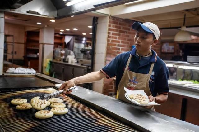 Daniel González prepara arepas en un restaurante de Caracas. El analista Miguel Octavio utiliza los precios de esta popular comida nacional para seguir la inflación en el país. PHOTO: MIGUEL GUTIÉRREZ PARA THE WALL STREET JOURNAL