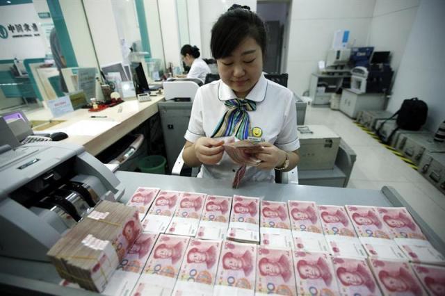 Una empleada cuenta yuanes en una sucursal bancaria en Huaibei, en la provincia de Anhui (China) hoy, 26 de agosto de 2015. La intervención de urgencia del banco central chino de este martes estabilizó hoy, 26 de agosto de 2015, las bolsas asiáticas, que suavizaron sus caídas en China y Hong Kong y se recuperaron en el resto del continente. EFE/Woo He