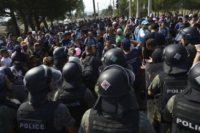 Inmigrantes controlados por la policía macedonia cruzan la frontera entre Macedonia y Grecia, cerca de Gevgelija (Macedonia) hoy 26 de agosto de 2015. Macedonia sigue permitiendo la entrada de refugiados a través de su frontera con Grecia y, aunque la situación es de calma, persiste la preocupación por la llegada diaria de miles de personas. Según datos ofrecidos por el ministro del Interior macedonio, Mitko Cavkov, solo el pasado sábado llegaron a Gevgelija, la primera ciudad tras la frontera, 8.000 refugiados, lo que equivale a un tercio de la población de la ciudad. EFE/Vassil Donev