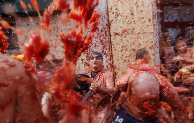 Vista general de la Tomatina en la calle principal de la localidad valenciana de Buñol que celebra el 70 aniversario de su tradicional fiesta, en la que participan más de 22.000 personas de 96 nacionalidades diferentes y en la que se lanzarán 150 toneladas de tomate, una cifra récord. EFE/Kai Försterling