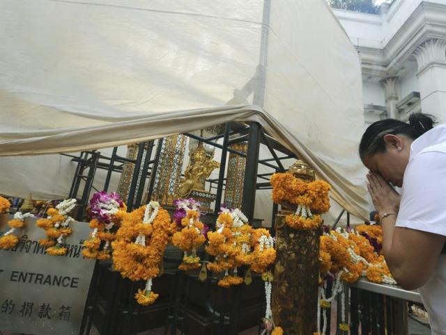 Una mujer reza ante la estatua de Lord Brahma en el templo de Erawan en Bangkok (Tailandia) hoy, 26 de agosto de 2015, antes de su cierre para llevar a cabo trabajos de restauración después de que resultase dañado en la explosión del pasado 17 de agosto de 2015. EFE/Narong Sangnak
