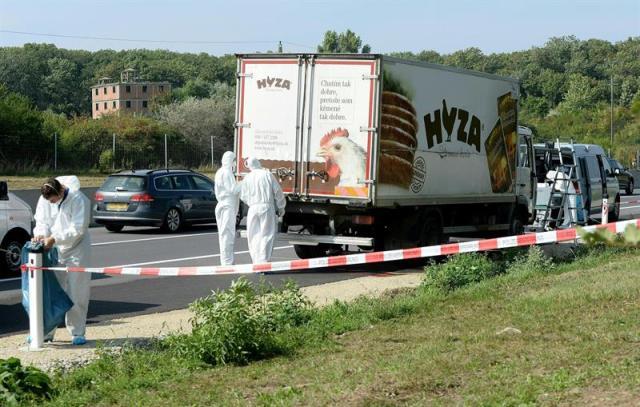 Expertos forenses realizan su trabajo en el camión frigorífico donde viajaba un grupo de inmigrantes que murieron asfixiados, en un arcén de la autopista A4, entre el lago Neusiedl y la localidad de Parndorf, en el Estado federado de Burgenland, Austria, hoy, 27 de agosto de 2015. Entre 20 y 50 refugiados, cuyas nacionalidades por el momento se desconocen, han muerto asfixiados cuando viajaban de forma ilegal por Austria en un camión. EFE/ROLAND SCHLAGER